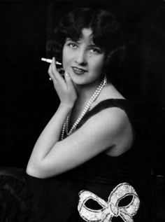 Fashionable woman with cigarette holder in hand wearing long double-strand pearl necklace.1924