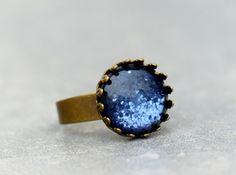 """Zarter Ring in einer """"Krönchen"""" Fassung. In die bronzefarbene  Ringfassung wurde ein schöner, blauer Resinstein eingesetzt. Die  Ringschiene ist in der Größe verstellbar. Somit ist..."""