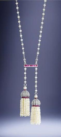 A Belle Époque pearl, ruby and diamond lavallière, by Andrey, probably for Cartier, circa 1910. The natural pearl and platinum chain connected by a calibré-cut ruby spacer via rose-cut diamond clasp mechanisms, suspending two seed pearl tassels of unequal length, each with a pierced cupola surmount millegrain-set with rose-cut diamonds and calibré-cut rubies, mounted in platinum and gold, maker's mark GA flanking a spray of mistletoe, French assay marks. #BelleEpoque #Cartier #Andrey…