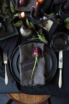 festliche tischdeko in schwarz, graue serviette, rose, besteck, kerze