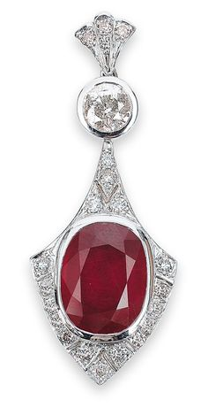 A ruby pendant 14 kt white gold, ca. 9.5 g, with 1 ruby, ca. 13 ct, 1 round brilliant-cut diamond, ca. 1.20 ct P/H and 19 round brilliant-cut diamonds, total ca. 0.75 ct P/K-N, length ca. 5 cm. Handmade.