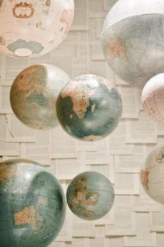 Hanging globes for either an office/travel room or as a mobile above a baby's crib. I also like whatever is going on in the background with the papers on the wall.