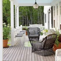 Open Season -  An abundant array of seating makes for a warm and inviting porch to enjoy with friends and neighbors. A lime green rug and  planters add a touch of color and celebrate the surrounding foliage.