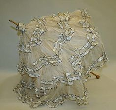 1900 ca. Light Fabric Parasol with rows of silver edging covering. metmuseum.org