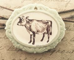 A personal favorite from my Etsy shop https://www.etsy.com/listing/245362545/jersey-cow-pendant-porcelain-cow-focal