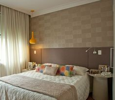 Este quarto, de 11 m², foi projetado pela designer de interiores Patricia K Pasquini. O ambiente traz um papel de parede que imita couro quadriculado, cabeceira estofada revestida com linho e um pendente amarelo.