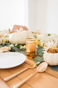 Gold gilded flatware, eucalyptus leaves, and colorful pumpkins...