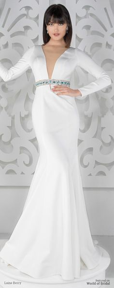 Heavy ottoman jersey fit and flare gown with long sleeves, dramatic plunging front and back V-necklines, belt features hand-placed Swarovski crystals with bright blue colored accents, sweep train.