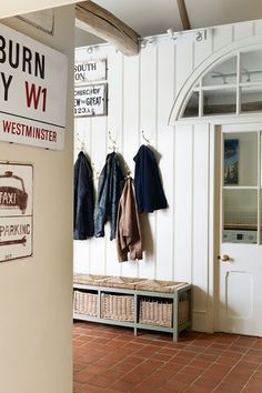 A small white hall with painted wood panelling, terracotta floor tiles and vintage inspired signage.