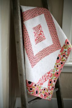 This modern baby quilt features black, white and pink patchwork on a stark white background. Quilted to perfection, this quilt is stunning.  This