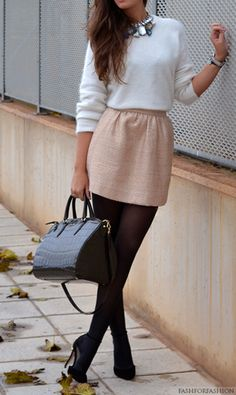 Outfit with a statement necklace, white sweater, champagne skirt, black tights and heels.