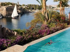 OLD CATARACT HOTEL, Aswan, Egypt - A felucca on the Nile sails by the hotel's swimming pool.