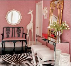 entry way foyer styling. pink walls. mirrored console table. zebra rug. brass faux bamboo mirror.