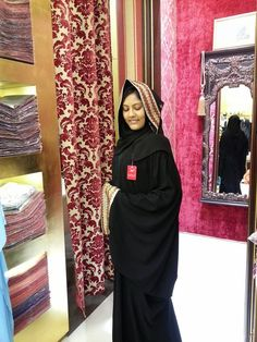 Black abaya with orange and gold trim - traditional ladies' attire from Artizana Ahjar, Dubai Mall Souk