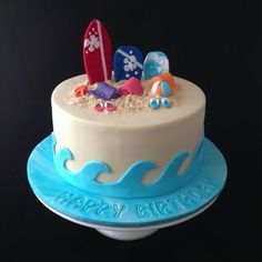 A beach themed cake for three beach babe sisters that all celebrate their birthdays in January! Complete with edible sand, surf board, boogie boards, beach towels, beach ball and thongs!