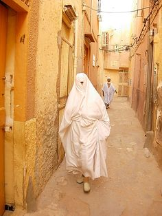 A woman in Algeria wearing a traditional 'haik', a white garment held in place with one hand, and often accompanied by the white lace 'ajar over the face. We Are The World, People Around The World, Around The Worlds, East Africa, North Africa, Cultural Diversity, African Countries, Folk Costume, Moorish
