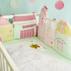 Tour de lit en coton composé de petites maisons imprimées brodées de taille différente. Coloris pastels rose, vert, bleu turquoise. Nouettes pour le fixer. Pour lits bébé 60x120 cm ou