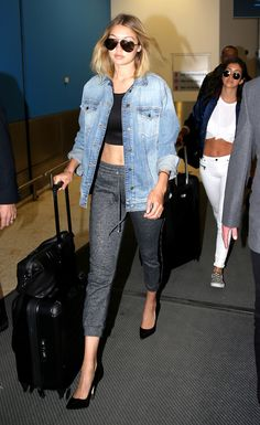 Gigi Hadid in gray sweatpants, a black crop top, denim jacket, and black pumps.
