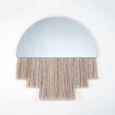 The Half Moon Mirror by Ben and Aja Blanc combines the functionality of a large sized mirror with the depth and textural interest of sculptural fiber.