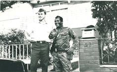"Soviet Angola veteran Igor Bukashev poses outside the ""villa DHW"" in Luanda, Angola with a Cuban guard."