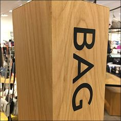 Natural Wood Post Signage creates space for a run of outfitting calling attention to clutches, small bags, and purse accessories