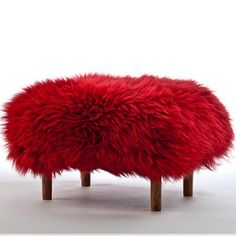 Bronwen in Dragon Red. . A luxury sheepskin footstool with stylish turned and tapered dark oak coloured legs and a removable real British sheepskin cover handmade in beautiful North. The Bronwen is definitely a slopping feet down stool. Just what you need after a long day!