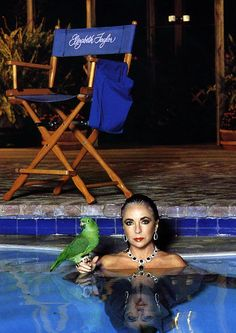Everything about this is badass - the parrot, the jewels, the make up, the pool... all of it.   Elizabeth Taylor by Helmut Newton