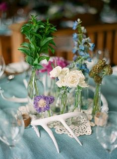 deer antler, doily, and old jars with wild flowers as center pieces.  Mis-matched table cloths made from old sheets and fabric.
