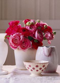 NATURAL BEAUTIES  Light and dark pink ranunculus share a simple salt-glaze crock. Play up the pink color palette and surround the bouquet with white- and pink-hued vessels. A polka-dot latte cup adds a touch of fun.