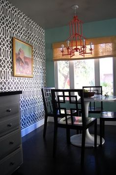 White Saarinen table, Asian inspired chairs, black/white accent wall, bright red chandelier, colorful painting, blue walls, white baseboard, grey ceiling