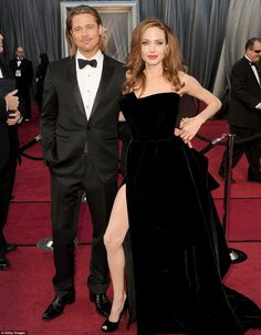 Oscar 2012 Angelina Jolie & Brad Pitt....Why is it EVERYTIME she stood still she had to stick her bony leg out that split??? I mean really...bony legs and knees are not her most flattering feature.