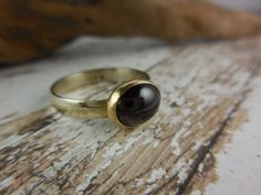 Made with garnet dark red gemstone cabochon, .925 sterling silver shank, and gold-over-brass bezel. Size 9