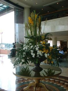 FOYER: oversized entry table arrangement of yellow helliconia, palm fronds, ...