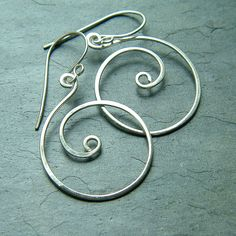Sterling silver coiled whirlwind hoops dangle from handmade sterling silver ear wires.  Shiny sterling silver wire spun into coils, then hammered to give it strength and to enhance the curves. Formed from 20 gauge sterling silver, then lightly buffed to a subtle shine.  These spiral silver earrings are approximately 3/4 inch wide (2cm), and hang 1 1/2 inches long (including the ear wires).   * Your silver earrings will arrive attractively gift boxed…