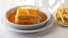 """Francesinha"" is a very popular dish in Porto. It is made with bread, wet-cured ham, linguiça, fresh sausage like chipolata, steak or roast meat, covered with melted cheese and a hot thick tomato and beer sauce. A classic francesinha meal would include the sandwich, surrounded on a bed of chips doused in the famous sauce"". Agosto no Porto é feito de francesinhas, marisco, bifes e leitão."