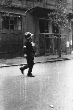 A Polish child courier, wearing the white armband of the Warsaw insurgents, crosses a street under fire. August 1944.
