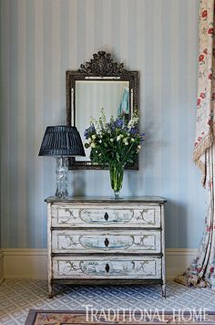 A crystal vase table lamp sits on an 18th-century Italian painted chest of drawers in this bedroom. - Photo: Francis Hammond / Design: Mark Gillette
