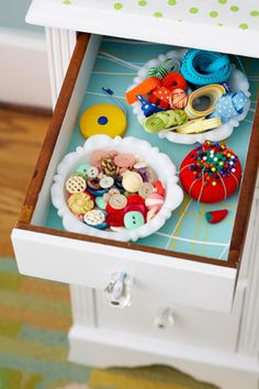 Decorate boring drawers with bright wallpaper or fabric. Keep notions in vintage jars.