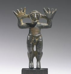 A BRONZE FIGURE OF A MAN, SYRO-PHOENICIAN(?), CIRCA MID 1ST MILLENNIUM B.C. standing in a lively pose with his big raised hands splayed wide, the face with short projecting beard, large beaked nose, and bulging eyes with prominent brows.  Height 2 5/16 in. 5.8 cm.