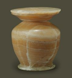 AN EGYPTIAN ALABASTER LIDDED KOHL JAR  MIDDLE KINGDOM, DYNASTY XI-XIV, 2040-1640 B.C.  The tapering piriform body with a short neck, wide disk rim and off-set disk base, the lid fitted with a central conforming projection  3 3/8 in. (8.6 cm.) high