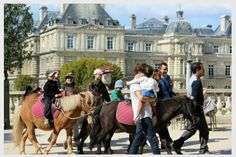 Luxembourg Gardens: Kids riding ponies in the park.