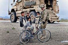 """Roadside chat  A paratrooper with the 82nd Airborne Division's 1st Brigade Combat Team teaches Afghan boys how to do the """"fistbump"""" April 22, 2012, in southern Ghazni province, Afghanistan. The soldier is part of a patrol securing Highway 1, the country's main highway between Kabul and Kandahar. (U.S. Army photo by Sgt. Michael J. MacLeod)"""