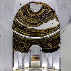 American artist Mark Bradford has turned the stately Palladian-style US Pavilion into a ruin. Visitors are greeted by litter scattered across the gravel outside, before entering the pavilion through a side door. The first room has a bulbous red and black mass hanging from the ceiling where it appears to have given way, and the central rotunda now has peeling and patchy walls.