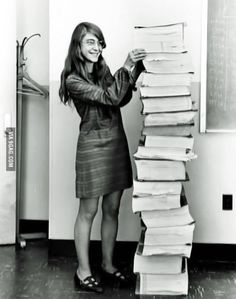 Margaret Hamilton, lead software engineer of the Apollo Project, stands next to the code she wrote by hand.