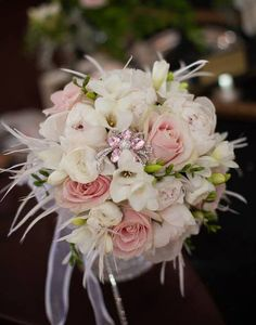 Gatsby inspired bouquet A beautiful bouquet inspired by the Great Gatsby….  white peonies, white ranunculus, white freesia, sweet akito rose, accented with a beautiful pink and crystal brooch and white feathers