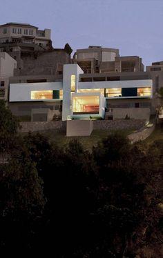 Tre volumi posti perpendicolarmente gli uni agli altri danno vita ad una composizione minimale che contrasta profondamente con la topografia naturale del paesaggio collinoso di Lima, in Perù.La struttura sorge lungo uno dei fianchi delle colline di...