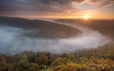 The sun rises over the Forest of Dean and the River Wye valley as seen from Symonds Yat Rock