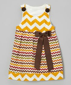 Warm, earthy colors light up this pretty little frock. With a cheerful zigzag pattern and bow at the waist, it's a sure favorite for family get-togethers and special events. The soft cotton construction stays comfy, while buttons on the shoulders make changing easy as pie. CottonMachine wash; tumble dryImported...