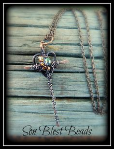 Beautiful wire cross & heart pendant / necklace. Created with oxidized copper wire and faceted glass beads. By artist, Kimi Springer of Son Blest Beads http://www.ebay.com/sch/sonblestbeads/m.html?item=281167463243&pt=Handcrafted_Artisan_Jewelry&hash=item4176e3034b&rt=nc&_trksid=p2047675.l2562