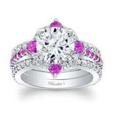 This unique pink sapphire and diamond halo engagement ring features a prong set round diamond center embellished with pink sapphires and diamond melee for a twist on the traditional halo ring. The narrow shank is adorned with shared prong set pink sapphires. Two shared prong set diamond weds nest up against the engagement ring  for an elegant finish.